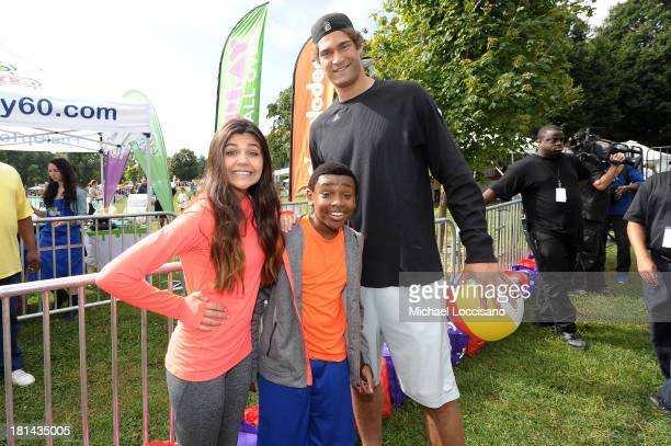 Actress Amber Montana NBA Player Brook Lopez and actor Curtis Harris pose for a photo as kids and families enjoy the activities at Nickelodeon's 10th...