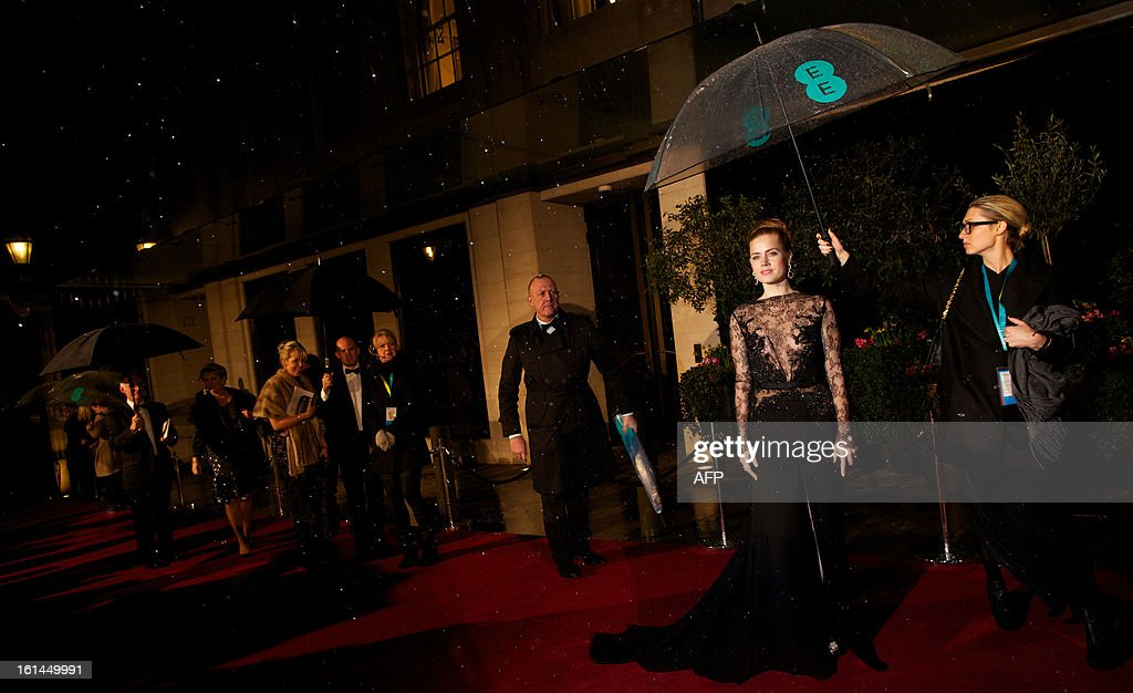 US actress Amy Adams shelters under an umbrella as she arrives for the BAFTA British Academy Film Awards after party in London on February 10, 2013.