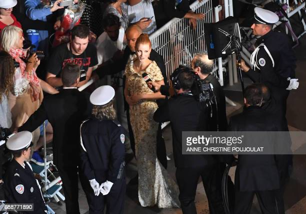 US actress and member of the Feature Film jury Jessica Chastain addresses a television reporter as she meets with fans while arriving on May 26 2017...