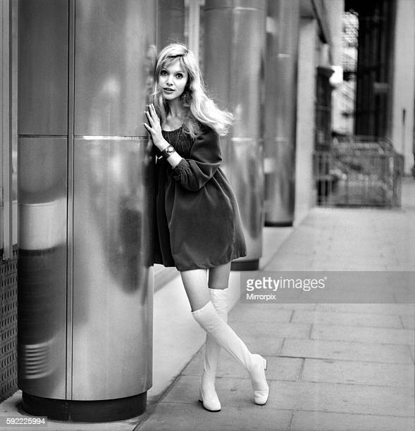 Actress and model Maddy Smith aged 20 photographed in London wearing a black dress and fwhite knee high boots November 1969 Z10608006