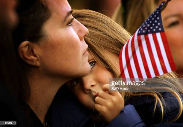 Actress and photographer Koo Stark holds her daughter during a memorial service for victims of the US terrorist attacks September 14 2001 outside St...