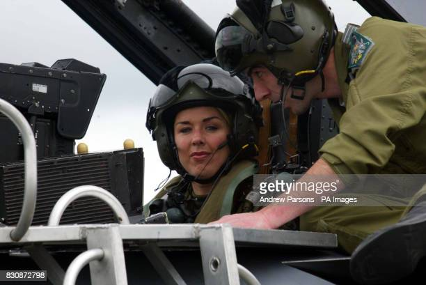 Actress and singer Claire Sweeney is briefed by Ft Lt Bob Yorston aas she sits in a Tornado GR4 of No IX squadron at RAF Marham in Norfolk before...