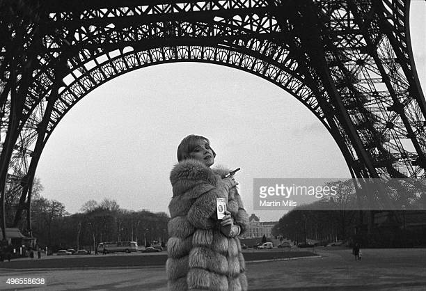 Actress and singer Edie Adams poseswith a pack of Muriel cigars in front of the Eiffel Tower in Paris France