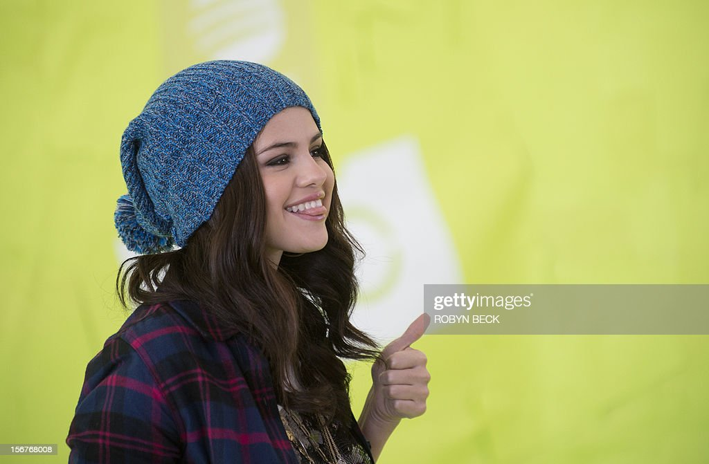 Actress and singer Selena Gomez gives the thumbs up as she models NEO clothing in her new role of 'global style icon' and guest designer for NEO, a line of 'shoes and clothes for living in the now and making the most of every minute,' on November 20, 2012 in Los Angeles. The NEO label is part of the Adidas family of casual and sports fashion. AFP PHOTO / Robyn Beck