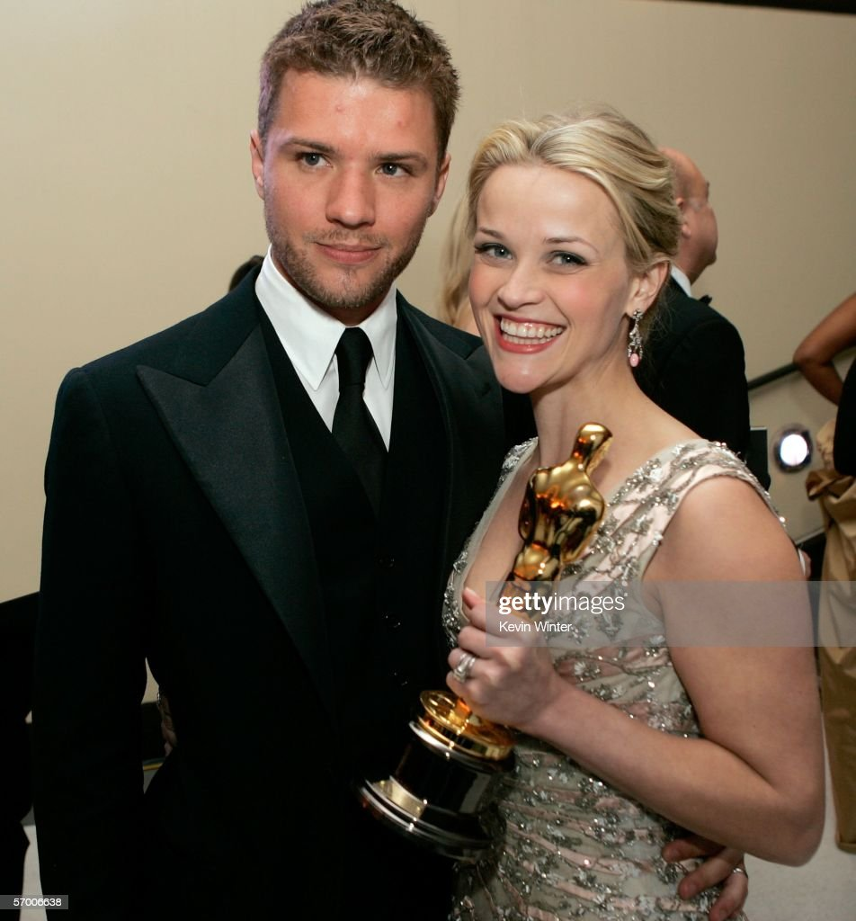 Actress and winner Reese Witherspoon poses with her Oscar and husband Ryan Phillippe as they attend the Governor's Ball after the 78th Annual Academy...