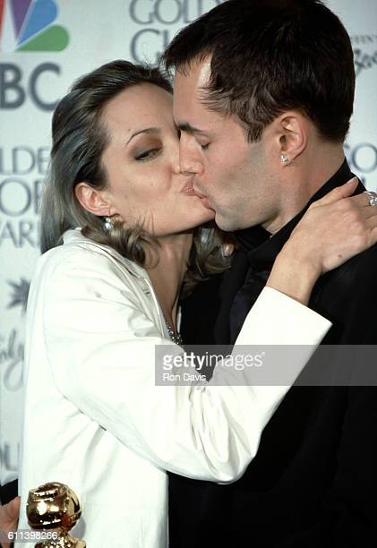Actress Angelina Jolie kisses her brother James Haven during 57th Annual Golden Globe Awards Press Room at the Beverly Hilton Hotel on January 23...