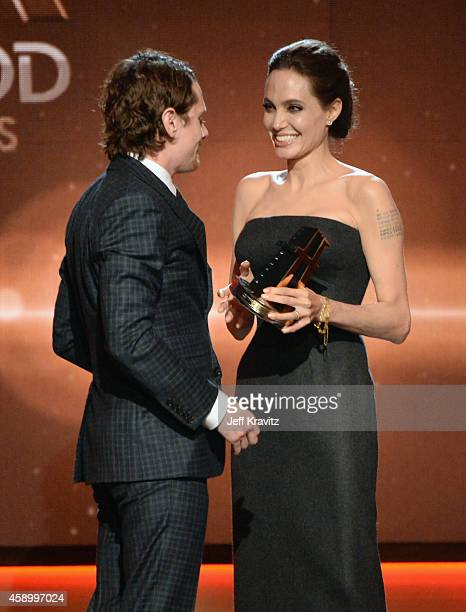 Actress Angelina Jolie presents honoree Jack O'Connell with the New Hollywood Award onstage during the 18th Annual Hollywood Film Awards at The...