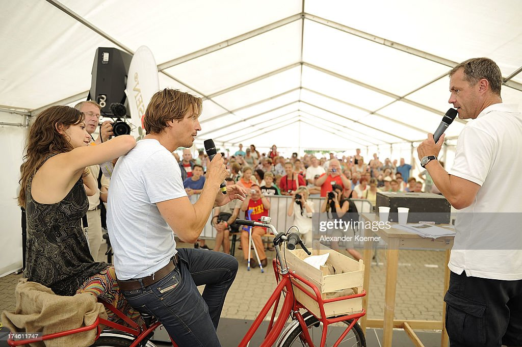Actress Anika Lehmann, actor Hakim Michael and actor Joachim Kretzer are beeing pictured on the famous red bike of the TV-character Naomi during the 'Rote Rosen Fan-Tag 2013' on July 28, 2013 in Luneburg, Germany. More than 3500 fans of the daily television telenovela 'Rote Rosen' came to see the Studios and to meet their favorite actor.