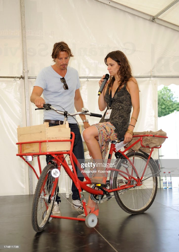 Actress Anika Lehmann and actor Hakim Michael are beeing pictured on the famous red bike of the TV-character Naomi during the 'Rote Rosen Fan-Tag 2013' on July 28, 2013 in Luneburg, Germany. More than 3500 fans of the daily television telenovela 'Rote Rosen' came to see the Studios and to meet their favorite actor.
