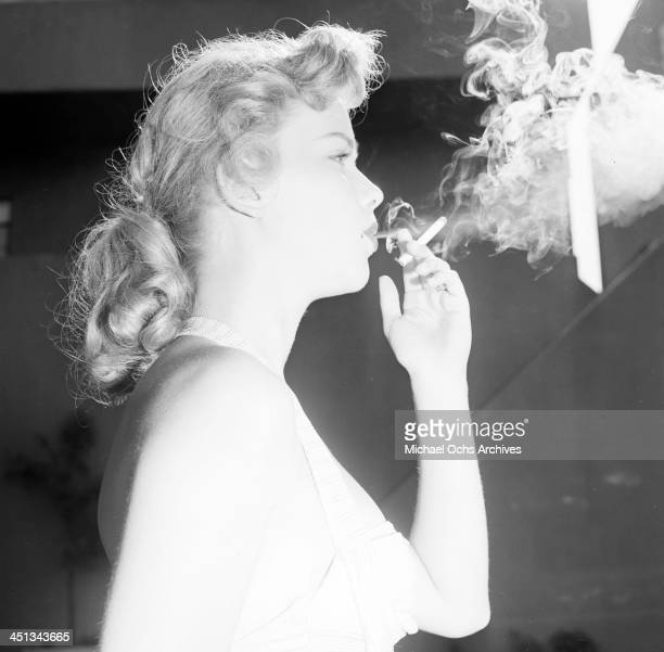 Actress Anne Francis poses as she smokes by the pool in Los Angeles California