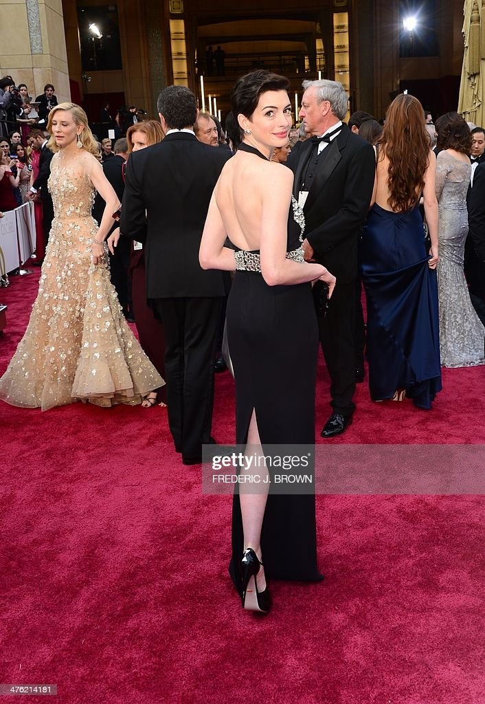 Actress Anne Hathaway (C) arrives on the red carpet for the 86th Academy Awards on March 2nd, 2014 in Hollywood, California. AFP PHOTO FREDERIC J. BROWN