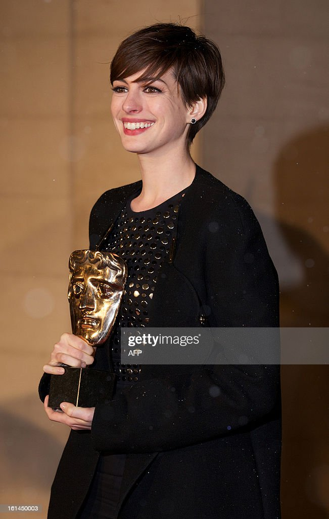 US actress Anne Hathaway poses with the award for best supporting actress for her performance in the film Les Miserables as she arrives for the BAFTA British Academy Film Awards after party in London on February 10, 2013. AFP PHOTO / ANDREW COWIE