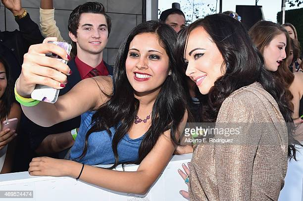 Actress Ashley Rickards poses for a selfie photo with a fan at The 2015 MTV Movie Awards at Nokia Theatre LA Live on April 12 2015 in Los Angeles...