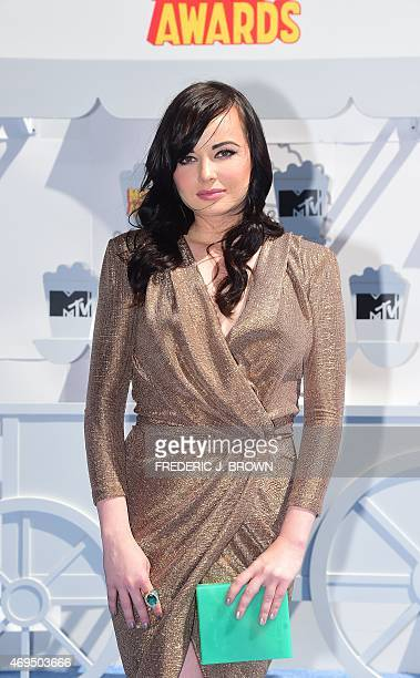 Actress Ashley Rickards poses on arrival for the 2015 MTV Movie Awards on April 12 2015 in Los Angeles California AFP PHOTO / FREDERIC J BROWN