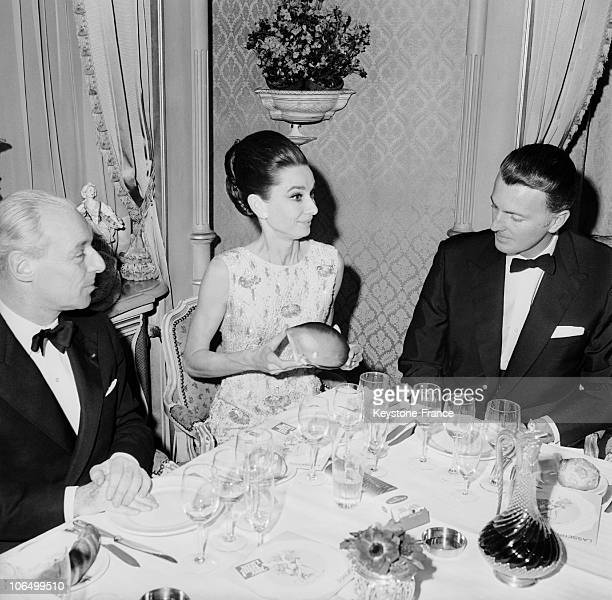 Actress Audrey Hepburg Between The Fashion Designer Hubert De Givenchy And The Baron Guy De Rothschild At The Bal Des Petits Lits Blancs In Paris On...