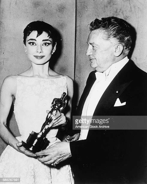 Actress Audrey Hepburn holding her Best Actress Oscar for the film 'Roman Holiday' with presented Jean Hersholt at the 26th Academy Awards New York...