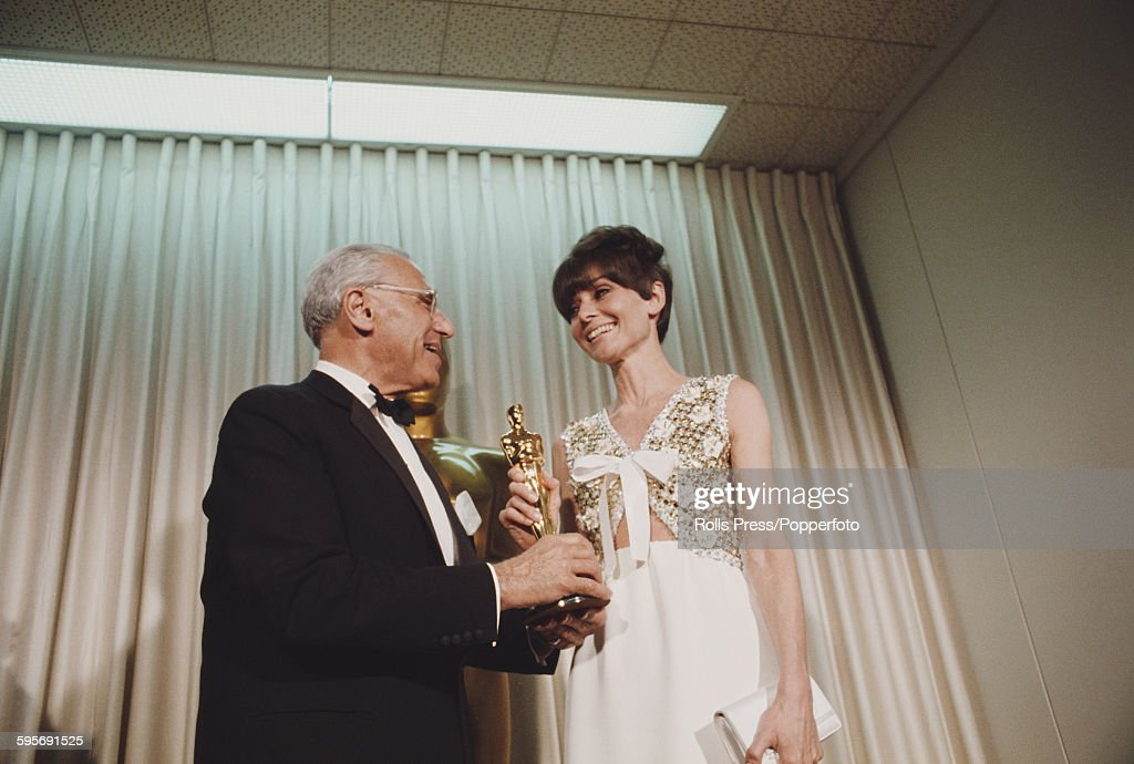 Actress <a gi-track='captionPersonalityLinkClicked' href=/galleries/search?phrase=Audrey+Hepburn&family=editorial&specificpeople=86470 ng-click='$event.stopPropagation()'>Audrey Hepburn</a> (1929-1993) pictured standing with American film director <a gi-track='captionPersonalityLinkClicked' href=/galleries/search?phrase=George+Cukor&family=editorial&specificpeople=226979 ng-click='$event.stopPropagation()'>George Cukor</a> (1899-1983) at the 40th Academy Awards at the Santa Monica Civic Auditorium in California on 10th April 1968. <a gi-track='captionPersonalityLinkClicked' href=/galleries/search?phrase=George+Cukor&family=editorial&specificpeople=226979 ng-click='$event.stopPropagation()'>George Cukor</a> is accepting the Best Actress Academy Award on behalf of Katharine Hepburn.