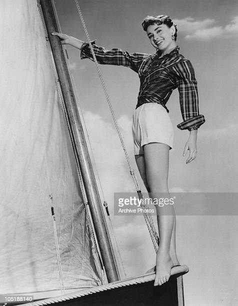 Actress Audrey Hepburn poses barefoot on a sailing boat on the set of the film 'Sabrina Fair' 1954