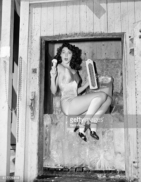 Actress Ava Gardner sits on a large block of ice while holding a thermometer in one hand and ice cream cone in the other