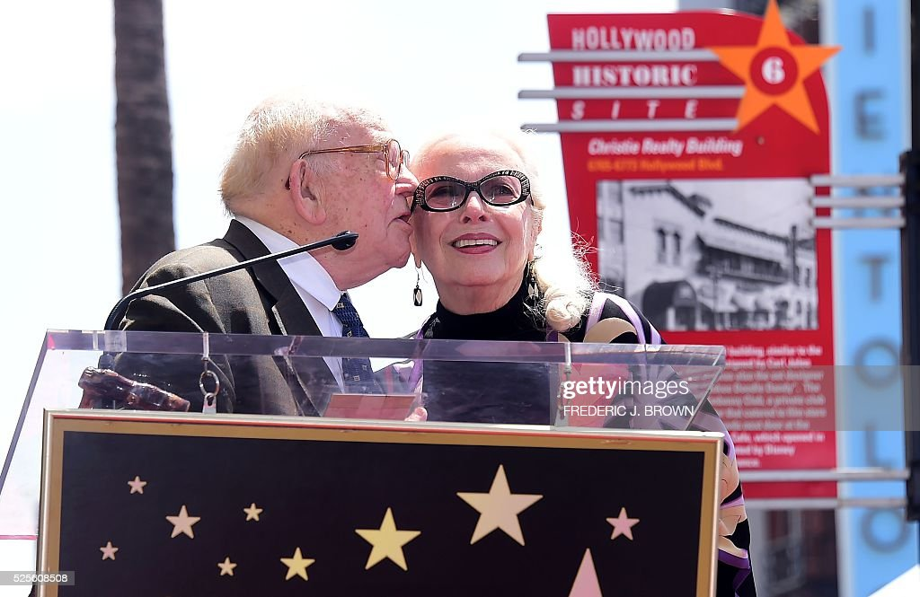 US actress Barbara Bain gets a kiss from Ed Asner during the ceremony for her Hollywood Walk of Fame Star in Hollywood, California on April 28, 2016. / AFP / FREDERIC