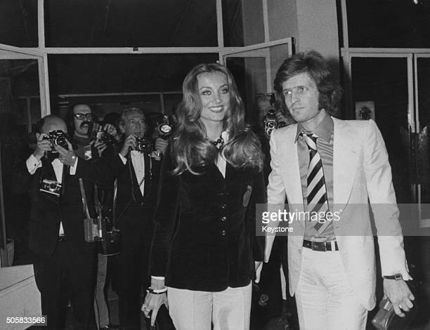 Actress Barbara Bouchet holding hands with Paolo Pazzaglia in front of a bank of press photographers as they attend the Cannes Film Festival France...