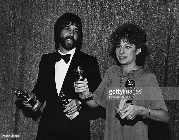 Actress Barbra Streisand and producer Jon Peters holding their awards for the film 'A Star is Born' at the Golden Globe Awards Los Angeles January...