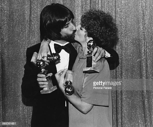 Actress Barbra Streisand and producer Jon Peters kissing as they hold their awards for the film 'A Star is Born' at the Golden Globe Awards Los...