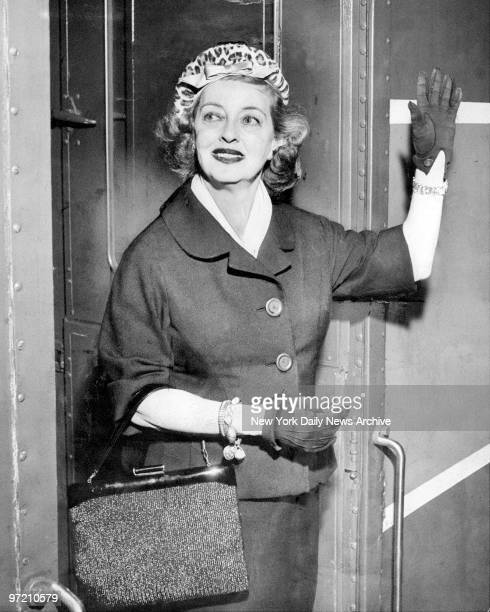Actress Bette Davis waves goodbye to fans as she boards a train at Grand Central Terminal for a trip to Hollywood