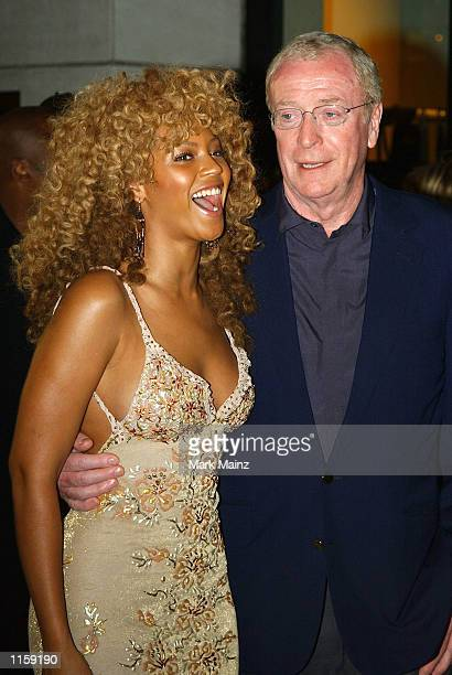 Actress Beyonce Knowles poses for photographers with actor Michael Caine at the 'Austin Powers Goldmember' party July 24 2002 at Barney's in New York...