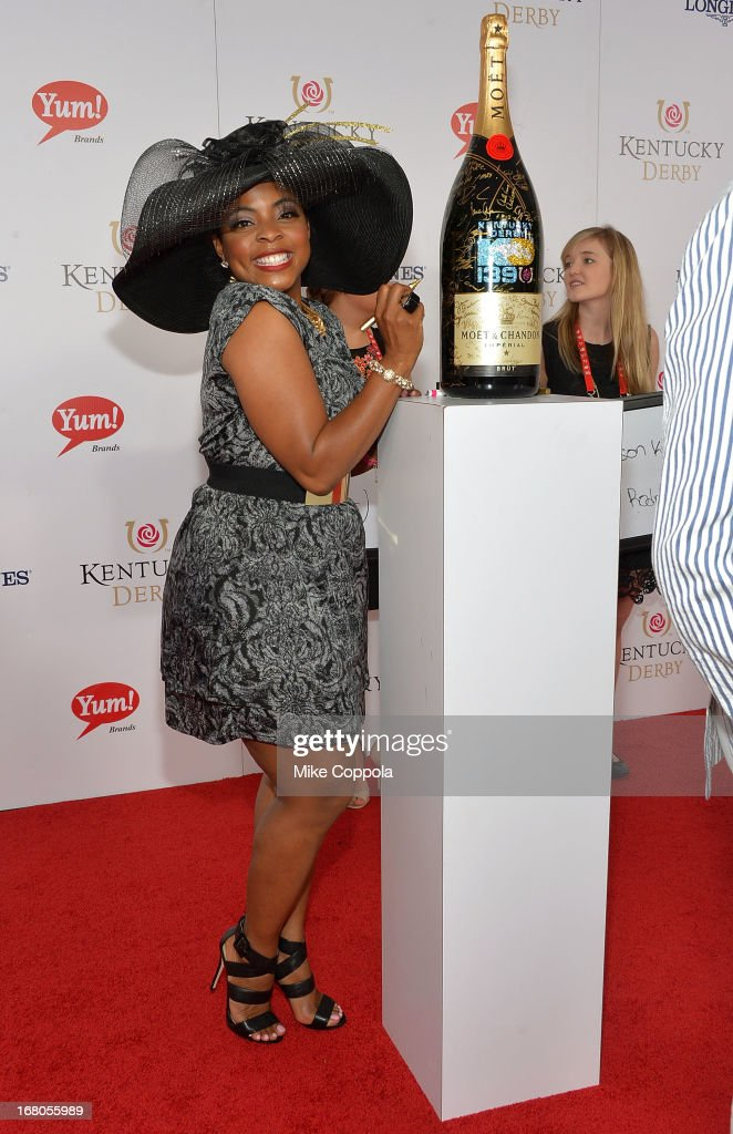Actress Brely Evans signs the Moet & Chandon 6L for the Churchill Downs Foundation during the 139th Kentucky Derby at Churchill Downs on May 4, 2013 in Louisville, Kentucky.