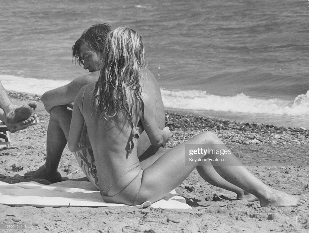 Actress <a gi-track='captionPersonalityLinkClicked' href=/galleries/search?phrase=Brigitte+Bardot&family=editorial&specificpeople=202903 ng-click='$event.stopPropagation()'>Brigitte Bardot</a> and her partner Patrick Gilles relaxing on a beach, during a break from filming 'Rum Runners', Almeria, Spain, 1970.
