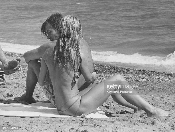 Actress Brigitte Bardot and her partner Patrick Gilles relaxing on a beach during a break from filming 'Rum Runners' Almeria Spain 1970