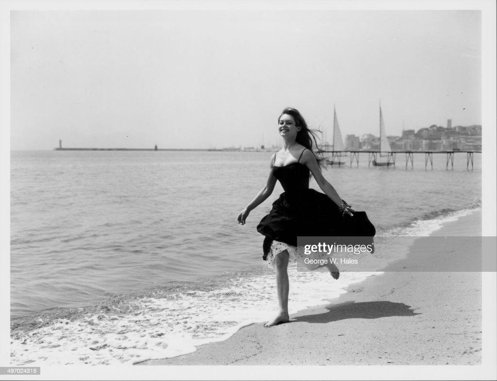 Actress Brigitte Bardot running barefoot along the beach Cannes France April 28th 1956