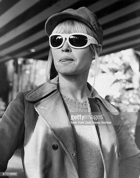 Actress Brigitte Bardot waits for her car outside a hotel in Hollywood