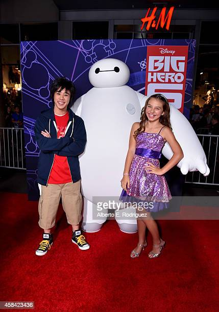 """Actress Caitlin Carmichael with characters Hiro and Baymax attends the Los Angeles Premiere of Walt Disney Animation Studios' """"Big Hero 6' at El..."""