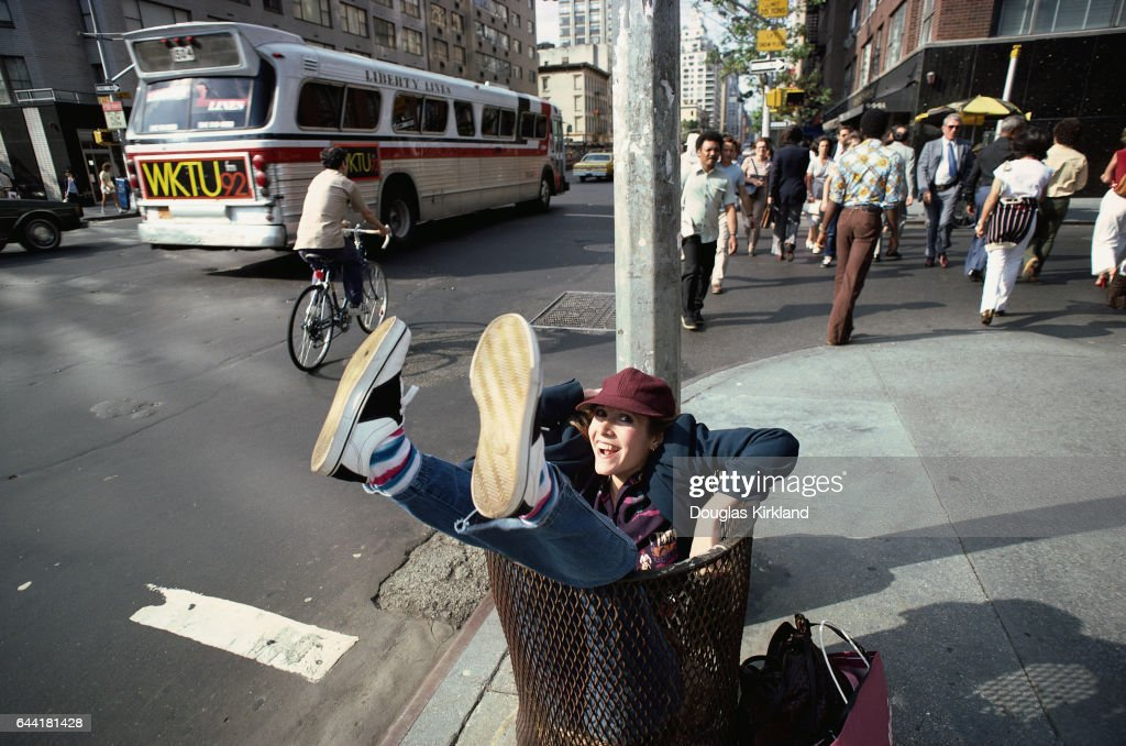 Actress Carrie Fisher sits in a garbage can on a New York street corner.