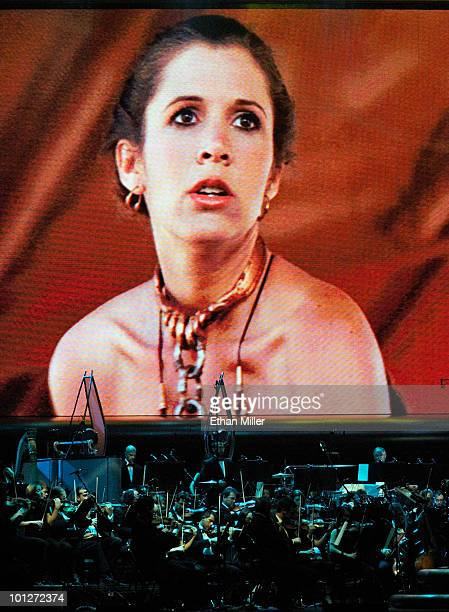 Actress Carrie Fisher's Princess Leia Organa character from 'Star Wars Episode VI Return of the Jedi' is shown on screen while musicians perform...