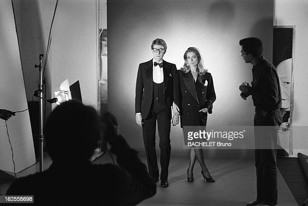 Actress Catherine Deneuve wearing YSL fashions poses with fashion designer Yves Saint Laurent in a photoshoot by German photographer Helmut Newton...