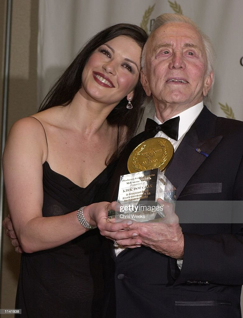 Actress Catherine ZetaJones and fatherinlaw Kirk Douglas recipient of the 'Milestone Award' pose for photographers at the Producers Guild of America...