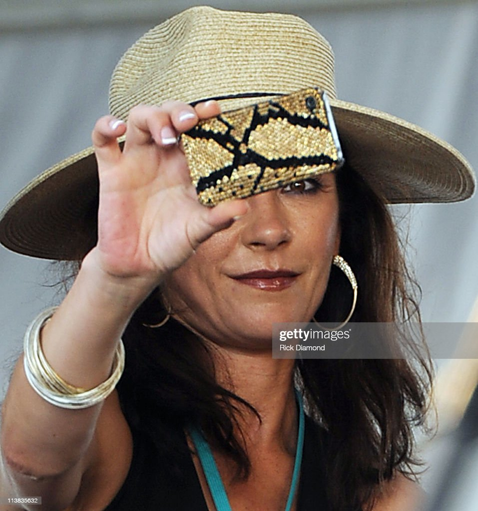 Actress Catherine Zeta-Jones photographs Singer/Songwriter Jimmy Buffett during the 2011 New Orleans Jazz & Heritage Festival - Day 6 presented by Shell at The Fair Grounds Race Course on May 7, 2011 in New Orleans, Louisiana.