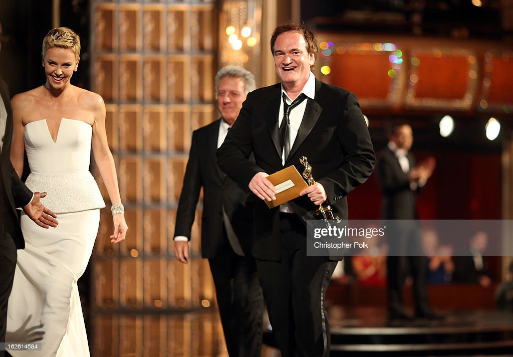 Actress Charlize Theron (L) and writer/director Quentin Tarantino, winner of the award for Original Screenplay for Django Unchained, onstage during the Oscars held at the Dolby Theatre on February 24, 2013 in Hollywood, California.