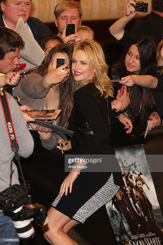 Actress <a gi-track='captionPersonalityLinkClicked' href=/galleries/search?phrase=Charlize+Theron&family=editorial&specificpeople=171250 ng-click='$event.stopPropagation()'>Charlize Theron</a> is photographed by fans at the 'Snow White And The Huntsman' photocall at Ritz Carlton Hotel on May 16, 2012 in Berlin, Germany.