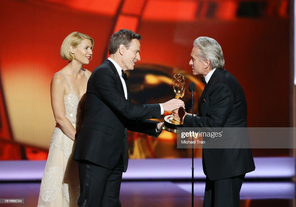 Actress Claire Danes and actor Bryan Cranston present an award to Michael Douglas onstage during the 65th Annual Primetime Emmy Awards held at Nokia...