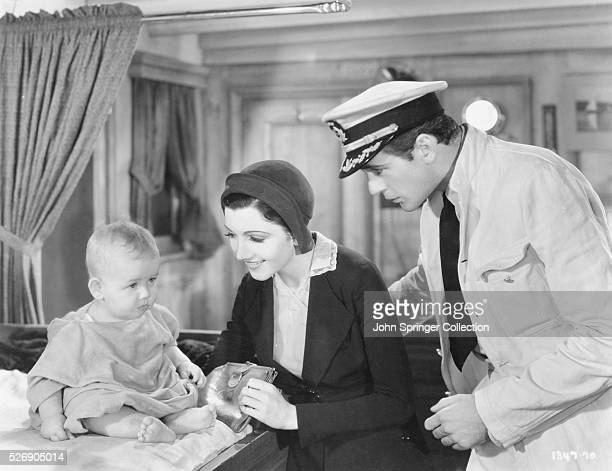 Actress Claudette Colbert and actor Gary Cooper star in a scene with an infant from the 1931 romance His Woman Cooper plays ship Captain Sam Whelan...