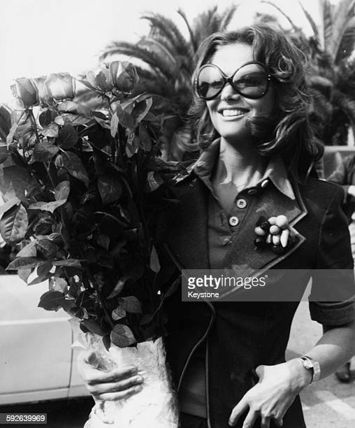 Actress Claudia Cardinale holding a bouquet of roses as she arrives at Rome Airport after attending the Cannes Film Festival Italy circa 1972