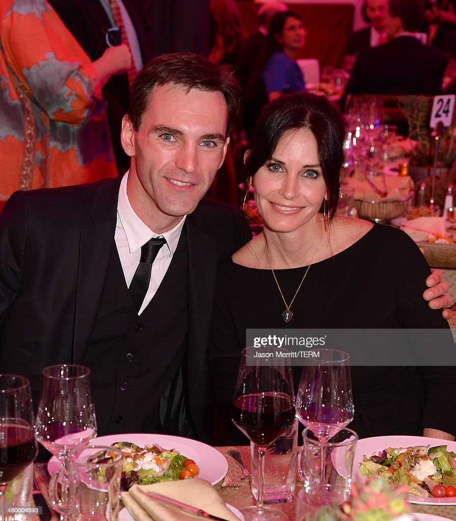 Actress <a gi-track='captionPersonalityLinkClicked' href=/galleries/search?phrase=Courteney+Cox&family=editorial&specificpeople=203101 ng-click='$event.stopPropagation()'>Courteney Cox</a> and <a gi-track='captionPersonalityLinkClicked' href=/galleries/search?phrase=Johnny+McDaid+-+Musicien&family=editorial&specificpeople=12322239 ng-click='$event.stopPropagation()'>Johnny McDaid</a> attend an Evening of Environmental Excellence presented by The UCLA Institute Of The Environment And Sustainability at Private Residence on March 21, 2014 in Los Angeles, California.