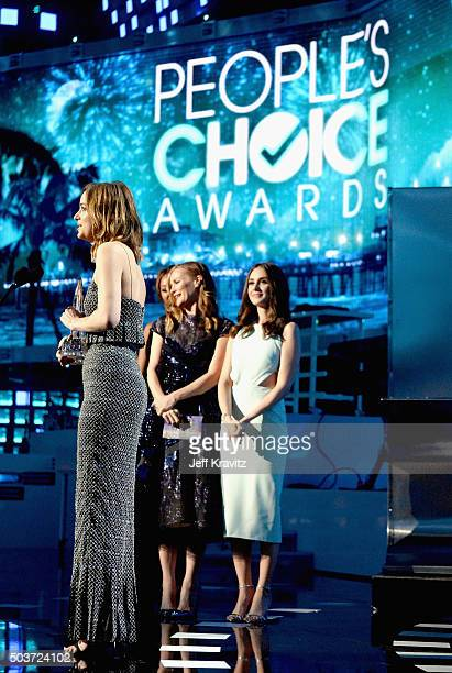 Actress Dakota Johnson accepts an award from actresses Leslie Mann and Alison Brie onstage during the People's Choice Awards 2016 at Microsoft...