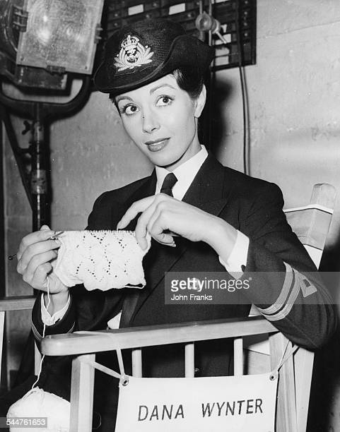 Actress Dana Wynter in a police uniform knitting baby clothes behind the scenes on the set of the film 'Sink the Bismarck' at Pinewood Studios circa...