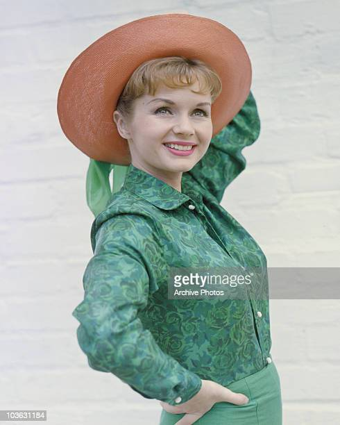 Actress Debbie Reynolds pictured smiling while posing in a green shirt and widebrimmed salmon pink hat circa 1960