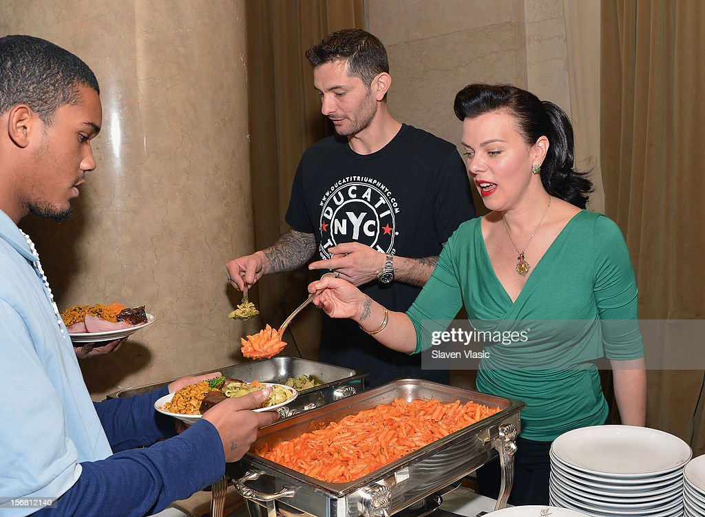 Actress Debi Mazar (R) and husband Gabriele Corcos volunteer during the Our Table Is Yours - A Thanksgiving Day benefit at Cipriani, Wall Street on November 21, 2012 in New York City.